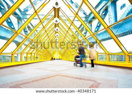 People silhouettes in motion in yellow passage, perspective view - stock photo