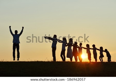 People silhouettes on summer sunset meadow making progress to success - stock photo