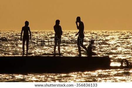 people silhouettes on the sea at sunset Family resting group of people summer vacation - stock photo