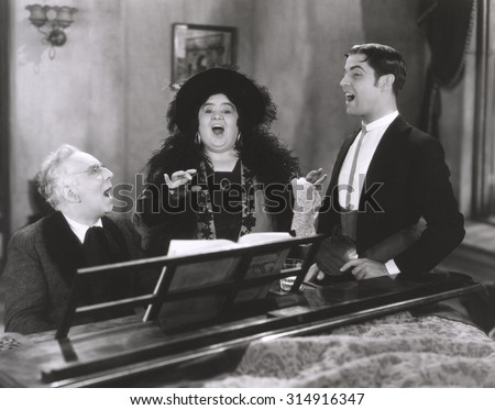 People singing at piano - stock photo