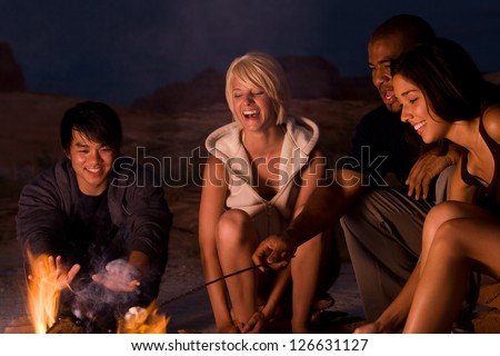 People sitting around a campfire at night - stock photo