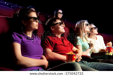 People sitting at the cinema, watching a film. Cinema photo series - stock photo