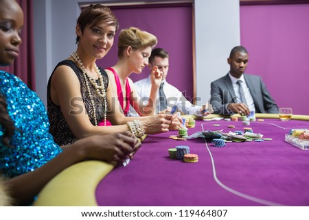 People sitting at the table of the casino smiling holding cards - stock photo