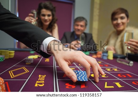 People sitting at the table while placing bets - stock photo