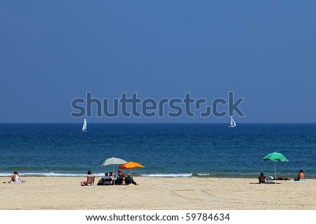 People sitting under umbrellas on a sandy sea beach and looking at white yachts - stock photo
