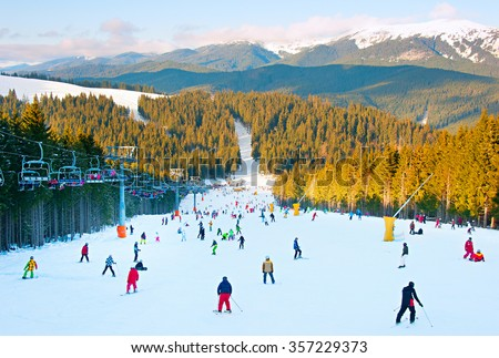 People skiing and snowboarding on a slope at ski resort - stock photo