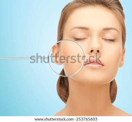 people, skin care and beauty concept - face of beautiful happy young woman over blue background - stock photo
