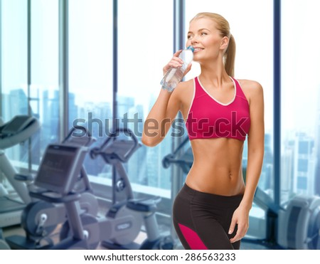 people, sport, fitness and recreation concept - happy woman drinking water from bottle over gym machines background - stock photo