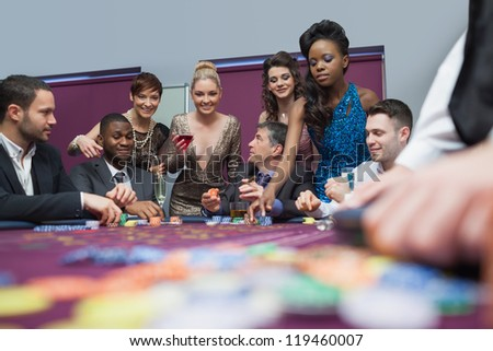People standing and sitting at the table enjoying roulette - stock photo