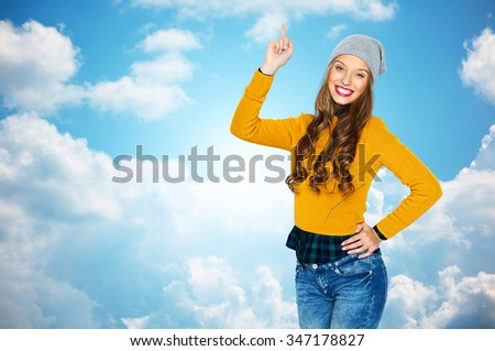 people, style and fashion concept - happy young woman or teen girl in casual clothes and hipster hat pointing finger up over blue sky and clouds background - stock photo