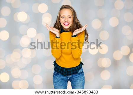 people, style and fashion concept - happy young woman or teen girl in casual clothes having fun over holidays lights background - stock photo