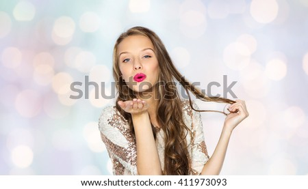 people, style, holidays, hairstyle and fashion concept - happy young woman or teen girl in fancy dress with sequins and long wavy hair sending blow kiss over holidays lights background - stock photo