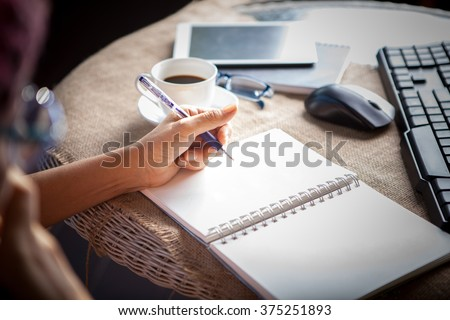 people taking mobile phone and  top table working by writing on white empty paper page with left hand  - stock photo