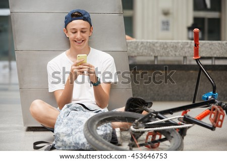 People, technology and communication concept. Handsome Caucasian 15-year old bike rider in street wear using wireless internet connection for communicating via social networks while relaxing outdoor - stock photo