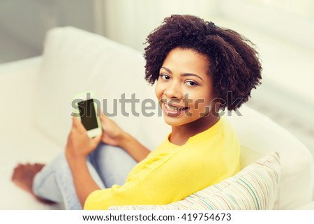 people, technology and leisure concept - happy african american young woman sitting on sofa with smartphone at home - stock photo