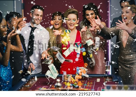 People throwing chips and cash on roulette table against snow falling - stock photo