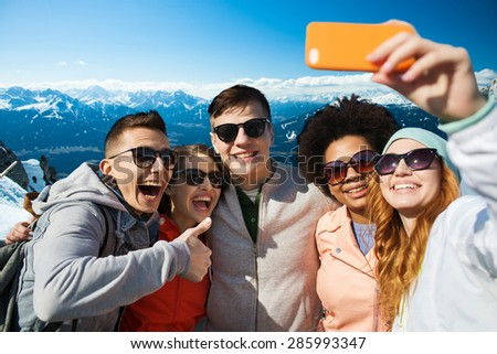 people, travel, tourism, friendship and technology concept - group of happy teenage friends taking selfie with smartphone and showing thumbs up over alps mountains in austria background - stock photo