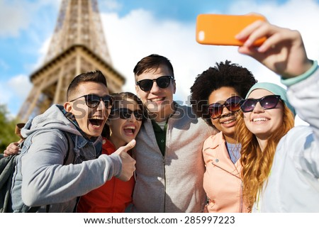 people, travel, tourism, friendship and technology concept - group of happy teenage friends taking selfie with smartphone and showing thumbs up over paris eiffel tower background - stock photo