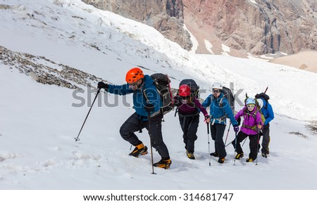 People traveling in mountains Large group of tourists of different sex ethnic nation race age young and old man woman walking up wild Snow Glacier terrain Steep Mountain Landscape in Background - stock photo