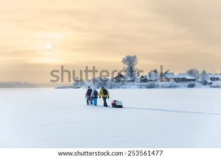 People traveling over frozen lake at beauty sunset, cold weather - stock photo