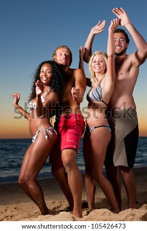 People (two couples) on the beach having a party, drinking and having a lot of fun in the sunset (people having bottles in their hands) - stock photo