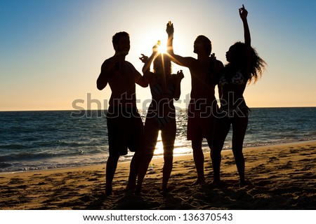 People (two couples) on the beach having a party, drinking and having a lot of fun in the sunset (only silhouette of people to be seen, people having bottles in hands with the sun shining through) - stock photo