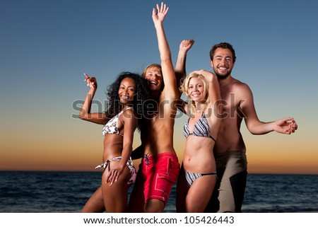People (two couples) on the beach having a party, having a lot of fun in the sunset - stock photo