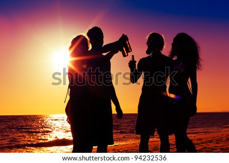 People (two couples) on the beach having party, drinking and having a lot of fun in the sunset (only silhouette of people to be seen, people having bottles in their hands with the sun shining through) - stock photo