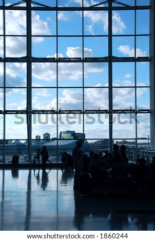 People waiting at the international airport terminal, bright blue sky outside - stock photo