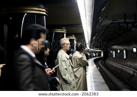 People waiting for a train in a Tokyo subway - stock photo