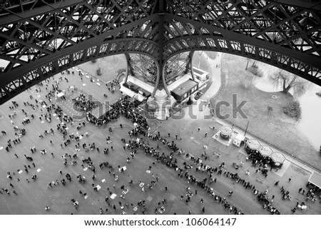 People waiting in line under Eiffel Tower in Paris France - stock photo