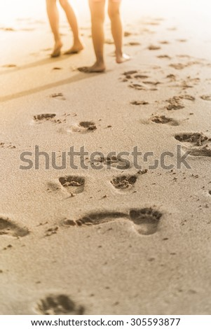 people walk on the beach with foot print behind - stock photo