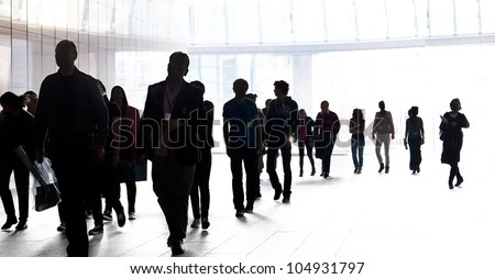 People walking against the light background of an urban landscape. Silhouettes. - stock photo