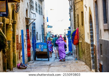 People walking along busy and narrow downtown street with buildings from both sides - stock photo