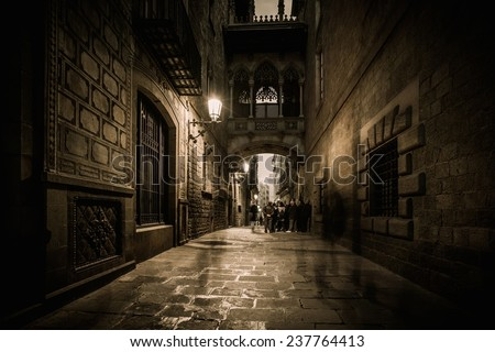 People walking at Carrer del Bisbe  in Barri Gotic, Barcelona - stock photo