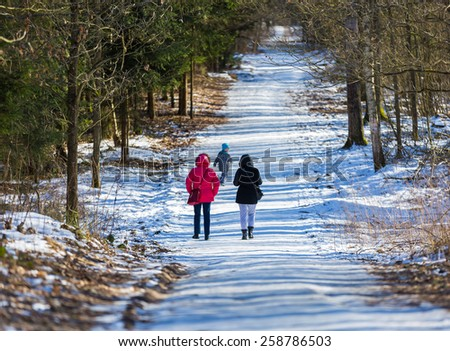 people walking in winter forest with child - stock photo