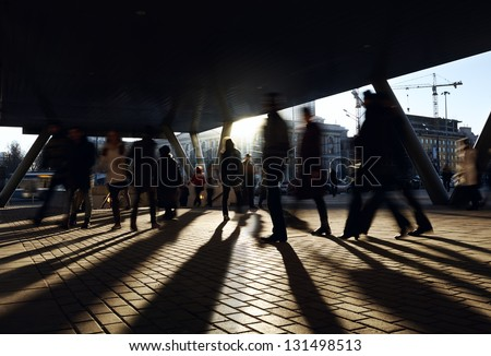 People walking near the metro station. City background with backlight sun. - stock photo
