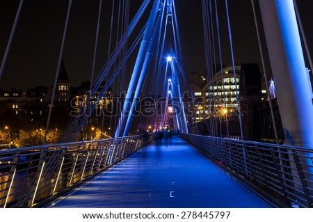 People walking on a modern bridge in London - stock photo