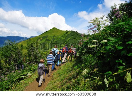 people walking on a path high in the mountains - stock photo