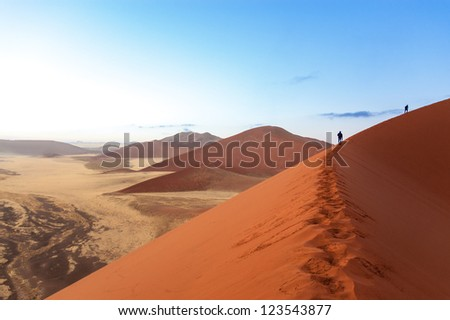 People walking on beautiful sunrise dunes of Namib desert, Sossusvlei, Namibia, South Africa - stock photo