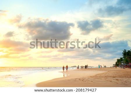 People walking on the beach of Sri Lanka at sunset - stock photo