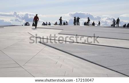 People walking on the marble roof of  the new opera house in Oslo, Norway - stock photo