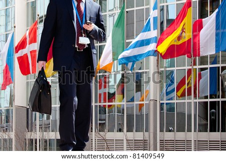 People Walking to Work. Flags with European Parliament in Brussels. - stock photo