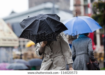 people walking with umbrellas in the rainy city - stock photo