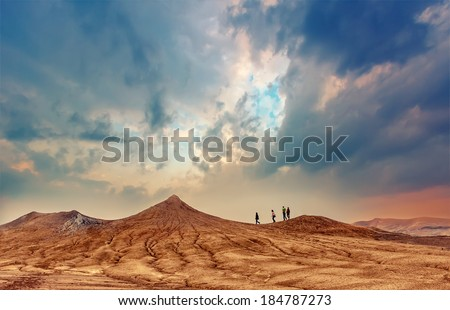 People walks on hills of active mud volcanoes in Buzau, Romania at sunrise. Dramatic sky colors and textured land. - stock photo
