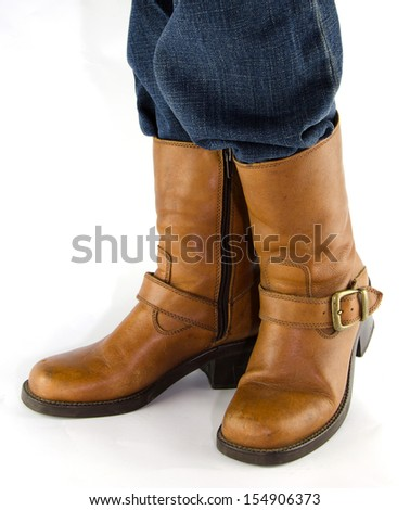 People wearing blue jeans, brown leather western cowboy  boots standing on white background. - stock photo