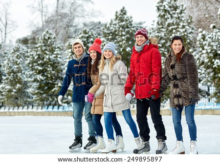 people, winter, friendship, sport and leisure concept - happy friends ice skating and holding hands on rink outdoors - stock photo