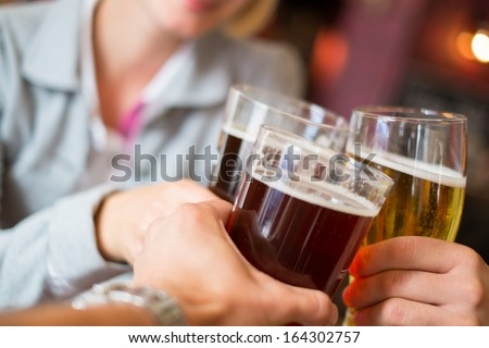 People with beer toasting in a pub  - stock photo