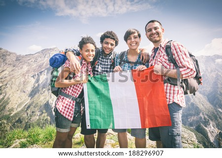 People with Italian Flag on top of Mountain - stock photo
