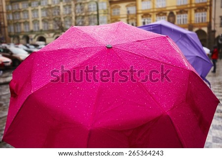 People with umbrellas in heavy rain - Prague, Czech Republic  - stock photo